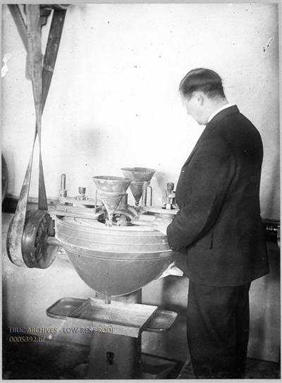 Unidentified Man Testing Stone for Hardness in a Dorry Abrasion Machine