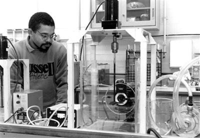 Grad student Joel Ducoste adjusts camera settings in a study of flocculation, 1996
