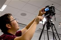 Jimmy He, a founding member of WaggleNet, sets up a camera to live stream the team's tri-weekly colloquium series.