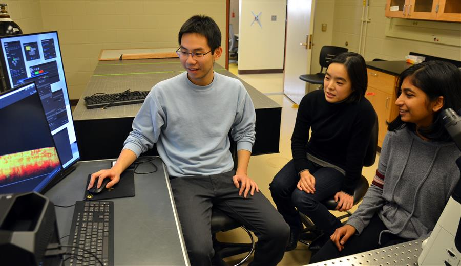 Professor Sangjin Kim (center) works with undergraduate students Zach Wang (left) and  Kavya Vaidya.