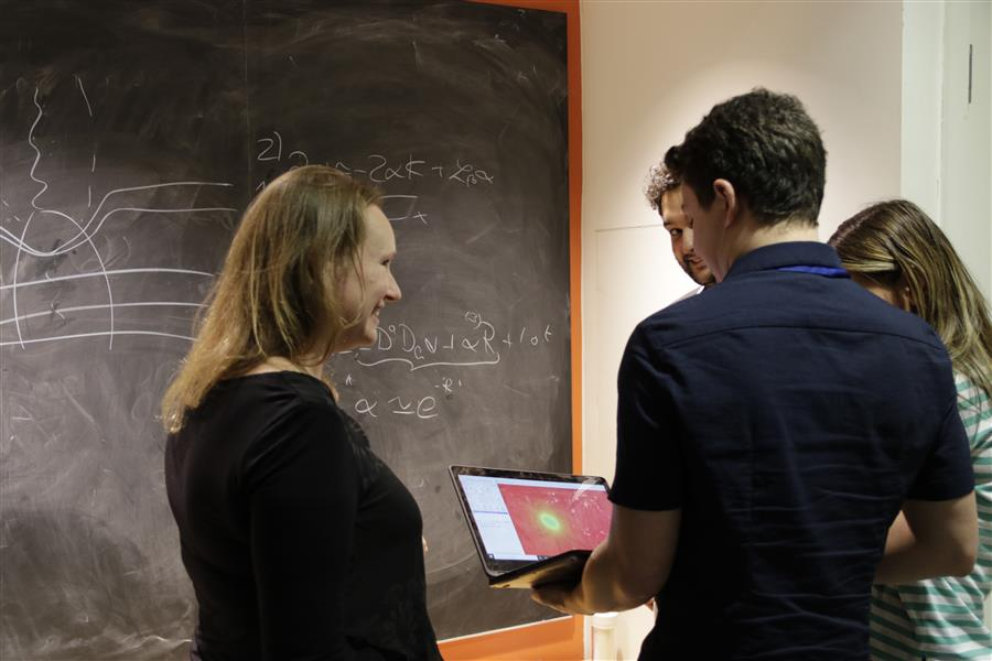 Professor Helvi Witek (left) discusses binary black hole simulations with Kings College London graduate students Matthew Elley (front), Guiseppe Ficarra (back, left) and Katarina Martinovik (back, right). Credit: Megan Grace-Hughes
