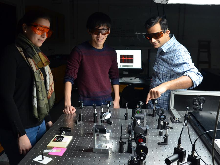 Professor Fahad Mahmood (right) works with graduate student Yinchuan Lu (center) and undergraduate student Andrea Perry (left) on generating and detecting THz radiation.