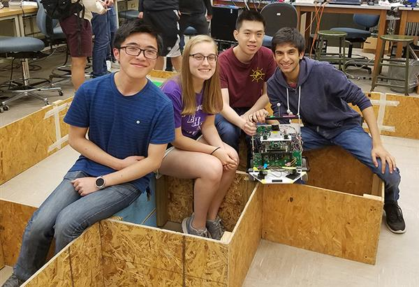 RuthAnn and her robotic mechatronics project. The Mechtronics (SE423) group worked on creating a wayfinding, weed-exterminating robotic car.  During that project, they worked with C programming, LabVIEW, and sensor data. Pictured are Keith Ng, RuthAnn Haefli, Hunter Ha Huynh, and Arjun Goradia.
