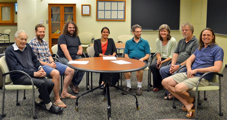 (L-R) Illinois Physics Professors Anthony Leggett, Lucas Wagner, Barry Bradlyn, Smitha Vishveshwara, Bryan Clark, Karin Dahmen, David Ceperley, and Taylor Hughes pause for a photo in the common room of the Institute for Condensed Matter Theory (ICMT) in Urbana. The Moore Foundation grant will support critical research projects involving all ICMT members. Photo by Siv Schwink for Illinois Physics