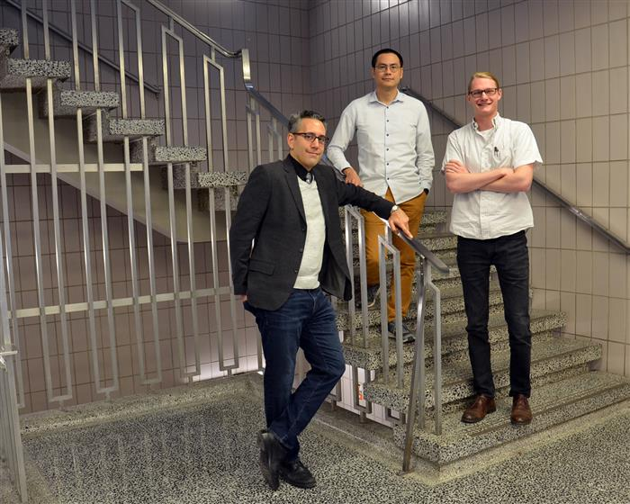 Illinois Physics Professor Nico Yunes (L) poses with with postdoc Hector Silva (middle) and graduate student Scott Perkins in the foyer of Loomis Laboratory of Physics. Photo by Siv Schwink for Illinois Physics