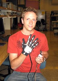 Photo of Jason Skowronski demonstrating sensor glove.