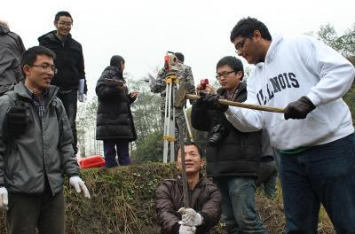 Karl Sengupta (r) and the Chongqing Jiaotong University students tested the depth of the soil at the bridge site. Being so far removed from the village Karl had to use a hammer and pole to get a measurement.