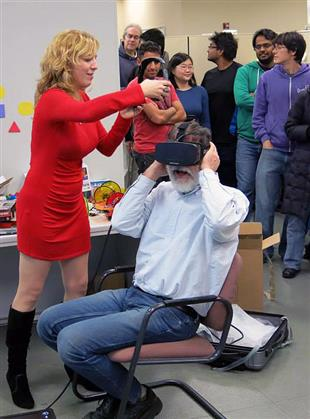 Anna Yershova, a CS alumna and Oculus research scientist helps Prof. Gerald DeJong try out the Oculus Rift HD prototype.