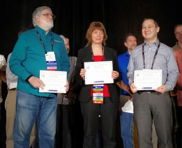 Illinois CS Teaching Assistant Professor Geoffrey Herman, right, accepts the award from SIGCSE with two of his co-authors, Assistant Professor Philip East of Northern Iowa University and education consultant and Harvey Mudd College instructor Lisa C. Kaczmarczyk.