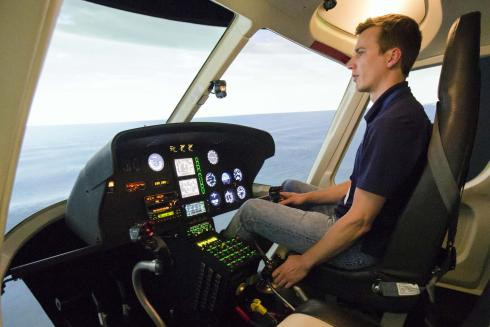 Chris Frost (BS, Aerospace Engineering, 2010) takes an AS 350 simulator for a virtual flight. He and his team are responsible for the flight and engine model and reactions to terrain.