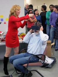 Anna Yershova, a CS alumna and Oculus research scientist helps CS Professor Gerald DeJong try out the Oculus Rift HD prototype.