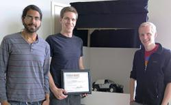The Lumenous team (from left): Raj Sodhi, Kevin Karsch, and Brett Jones. They are standing in front of the display they used for the Cozad competition. Karsch is holding the certificate they received when they won the Cozad competition.