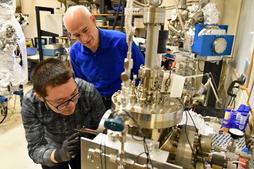 Postdoctoral researcher Gang Wang loading a sample into the system used to perform the nanotube crosslinking operation while Joseph Lyding looks on.