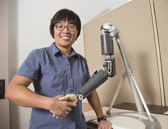 Liz Hsiao-Wecksler shaking hands with a robotic arm