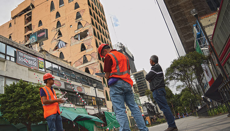 Hoskere, left, sends out a drone to automatically survey the facade of a heavily damaged building in Mexico City, while Neal, center, notes down details for a rapid visual assessment report under the supervision of Prof. Manuel Ruiz-Sandoval, right. The drone is visible over Neal's right shoulder.