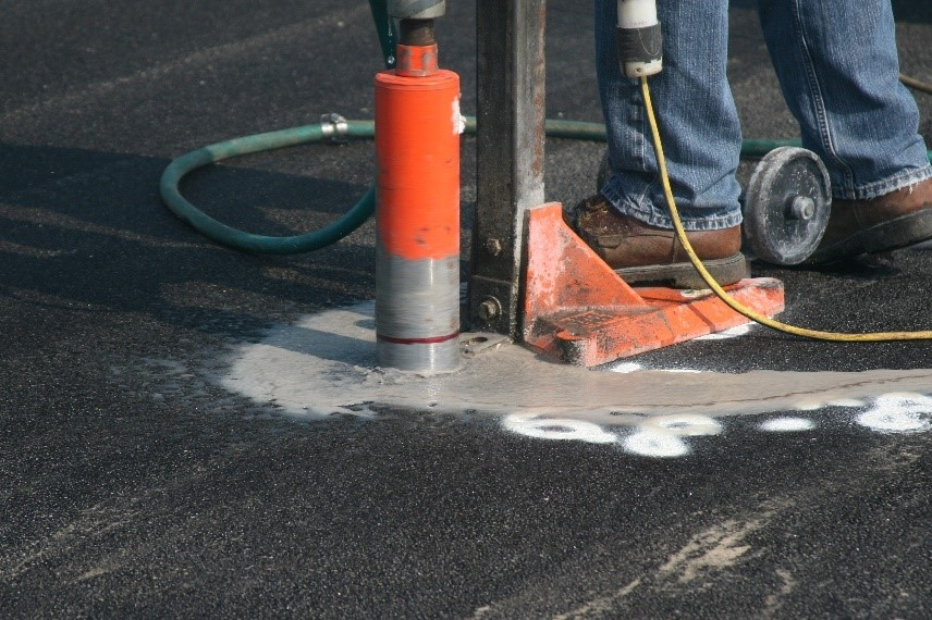 A contractor drills into an asphalt sample to measure its density — a major factor driving contractor pay disincentives.