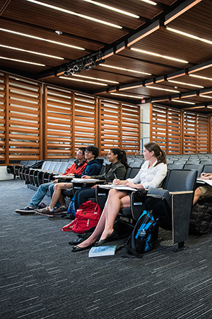 students sitting in lecture hall taking notes