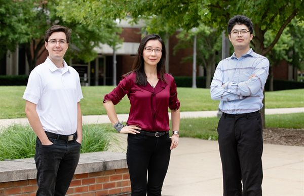 Mark Kraman, left, professor Xiuling Li, center, and Mike Yang, right, led a study that integrates the multiple elements needed for the electronic filters found inside wireless devices into a single, self-assembling and space-saving computer chip component.  Photo by L. Brian Stauffer