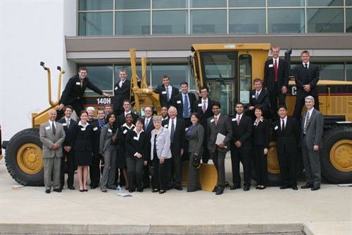 Hoeft T&M students pose with the Hoefts next to large construction equipment