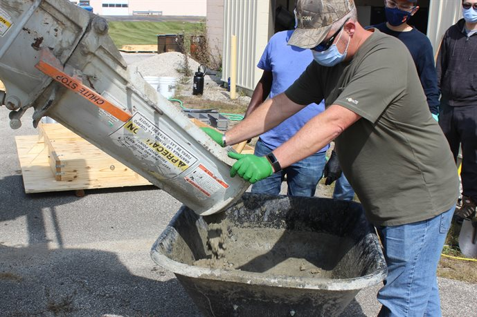 Greg Renshaw, ICT's senior research engineer, pours concrete to assist in the IDOT-sponsored project at ICT on Sept. 22.