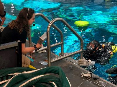 Katie Carroll, BS '19,  with diver at the NASA Neutral Buoyancy Lab pool