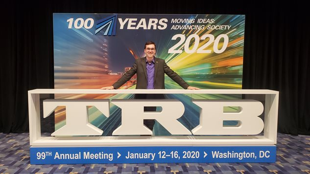 Leonel Evans, a UIUC master's grad, poses in front of the Transportation Research Board sign at the 99th annual meeting held in Washington, D.C. earlier in January.