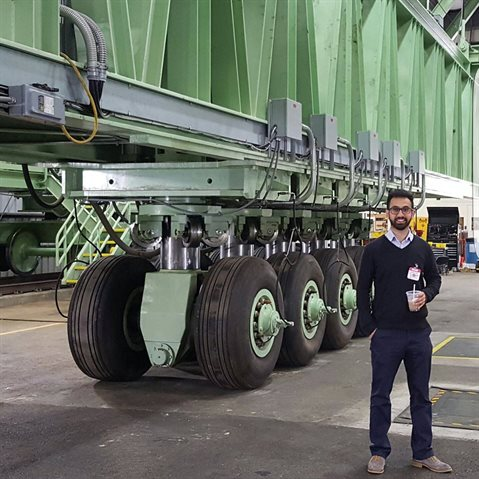 Erman Gungor, a UIUC doctoral grad, poses in front of one of the largest load simulators for aircraft loading at the Federal Aviation Administration's National Airport Pavement Test Facility near Atlantic City, New Jersey.