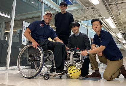 From left, University of Illinois wheelchair track team coach Adam Bleakney and graduate student researchers Chenzhang Xiao, Yu Chen and Seung Yun Song are shown Friday with the ballbot that will be used to drive their new PURE wheelchair at the Mechanical Engineering Laboratory. Photo by Chenzhang Xiao.