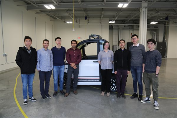 A group of staff and students in front of a smart car in the CSL High Bay.