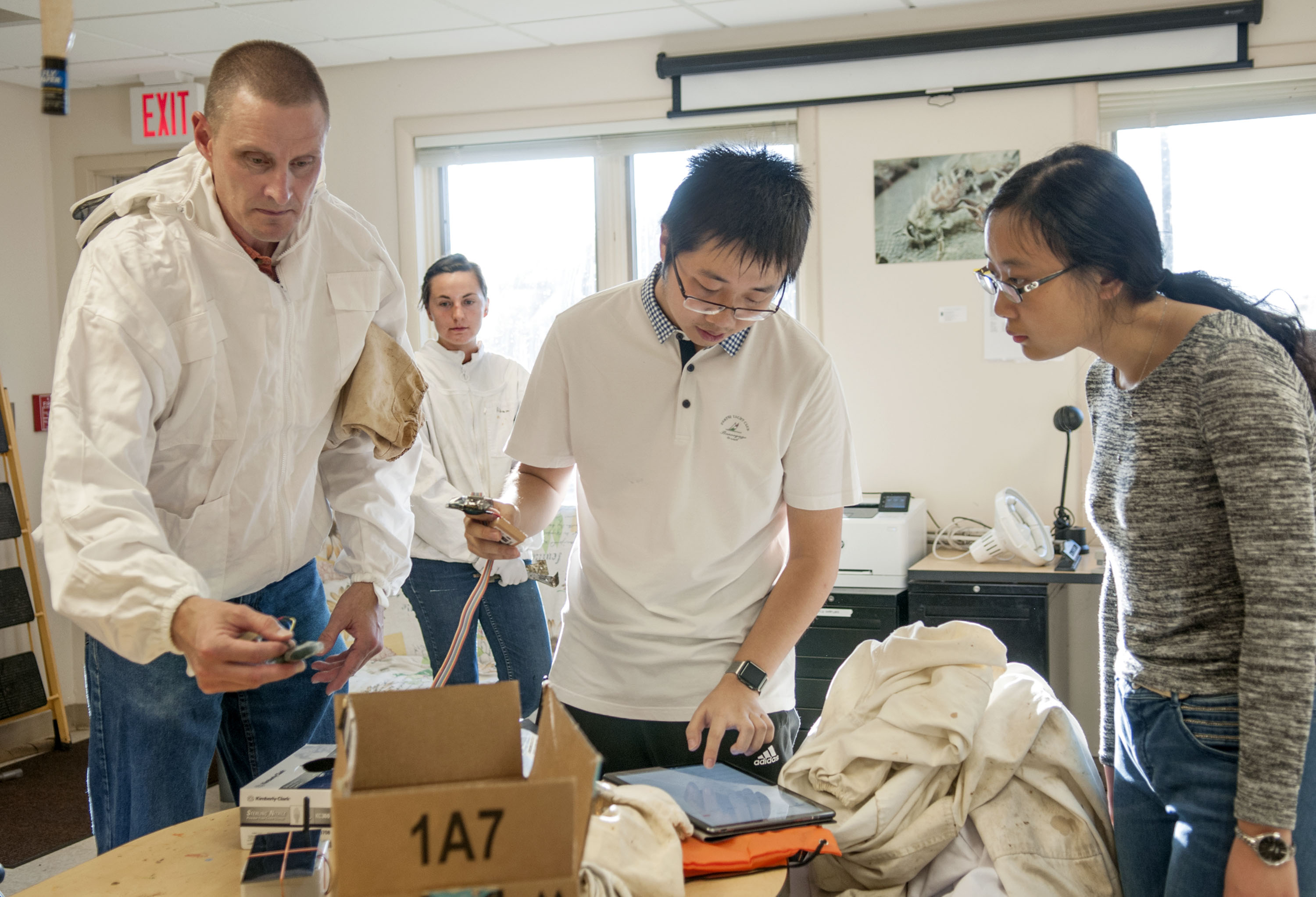Jimmy He checks the signal using a makeshift application to monitor a data stream, as WaggleNet team members, Chris Schmitz and Xiaolin Wu help to prepare deployment of the wireless monitoring system at the Bee Research Facility in Urbana. Beekeeper Ali Sankey (background left) is the lab manager and the team's first client.