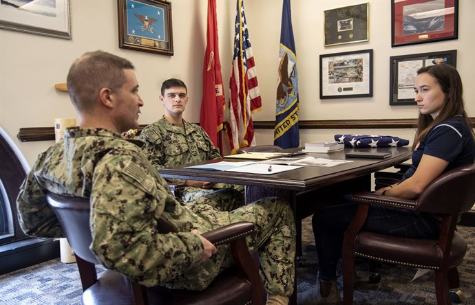 Lt. Daniel Meaney, USN, center, and Capt. Anthony Corapi, CO, &nbsp;University of Illinois NROTC, left, review a midshipman's fitness evaluation at the Navy ROTC offices at the UI Armory during early spring semester. Lt. Meaney's military family includes his father, Michael Meaney, chemical engineer and defense contractor; his grandfather, Thomas Meaney, radar engineer and defense contractor; an uncle, Robert Meaney, U.S. Marine Corps., platoon commander; to name a few. <em>Photo by Heather Coit</em>