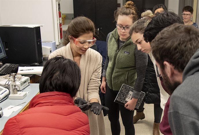 Molly Hein, center, gathers with her classmates to watch teaching assistant, Tooba Shoaib, demonstrate how to use a Differential Scanning Calorimetry in MSE 308 lab. Students were studying the range of temperatures by heating and cooling polymer samples, melting a solid to liquid, and vice versa.<br /><em>Photo by Heather Coit</em>